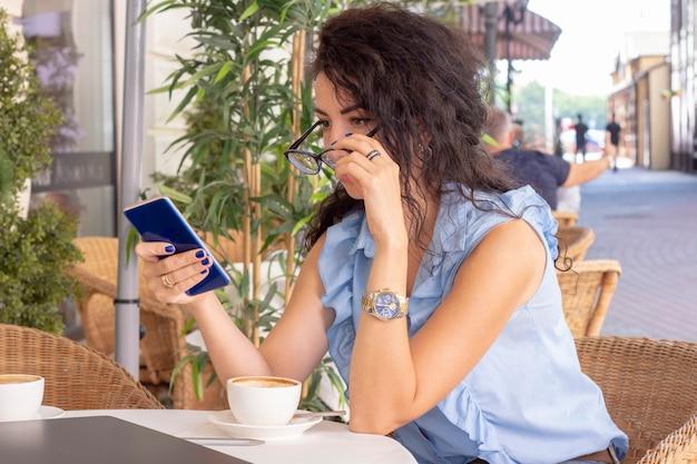 Femme en verre travaillant à distance avec ordinateur portable et téléphone au café.