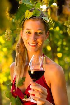Femme avec un verre de vin dans un vignoble