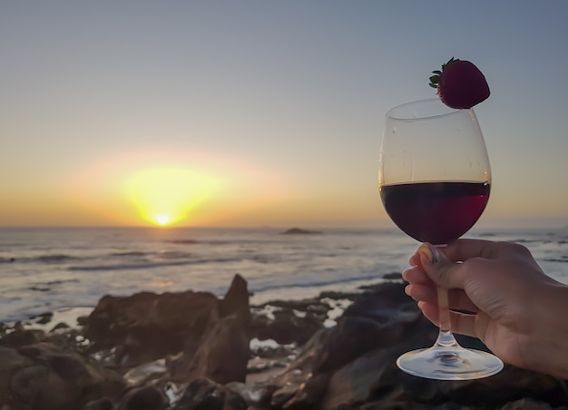 Femme avec verre de vin rouge et fraise sur la plage. coucher de soleil merveilleux moment