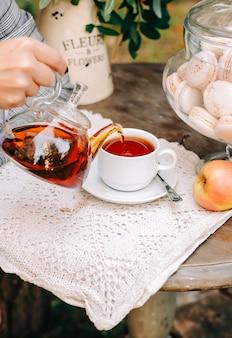 Femme versant du thé sur une tasse de théière en verre en plein air sur la table.