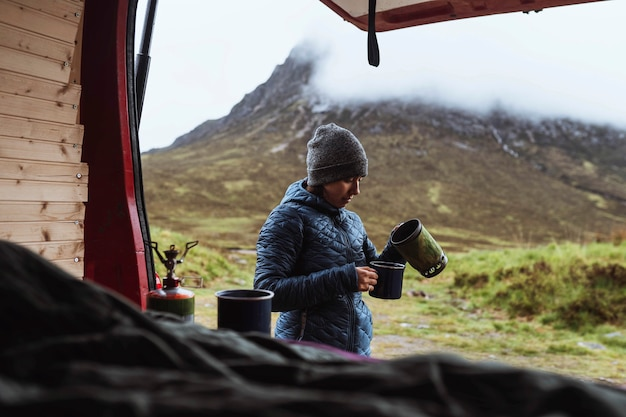 Femme versant de l'eau bouillante dans une tasse