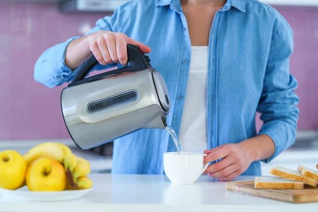 Femme versant de l'eau bouillie dans une tasse d'une bouilloire électrique pour préparer du thé chaud à la maison à la cuisine