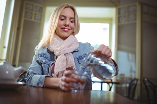 Femme versant de l'eau de la cruche en verre