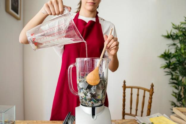 Femme versant de l'eau dans un mélangeur rempli de morceaux de papier