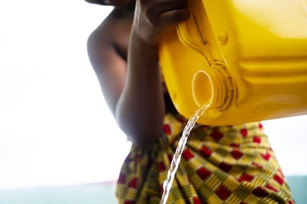 Femme versant de l'eau d'un récipient jaune