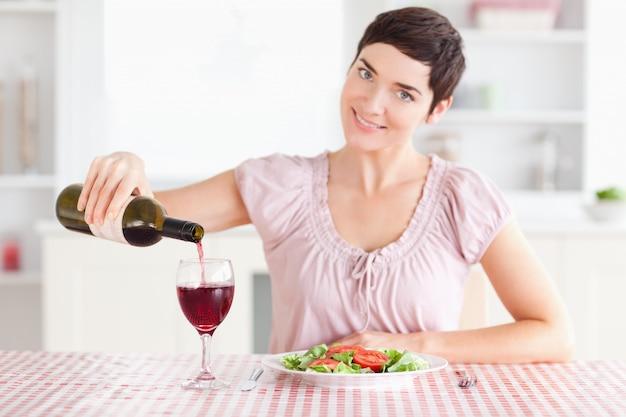 Femme versant le vin rouge dans un verre