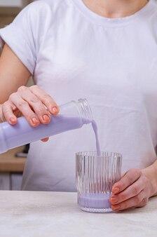 Une femme verse du lait de lavande dans un verre à partir d'une bouteille. boire un verre avec une paille. soins de santé