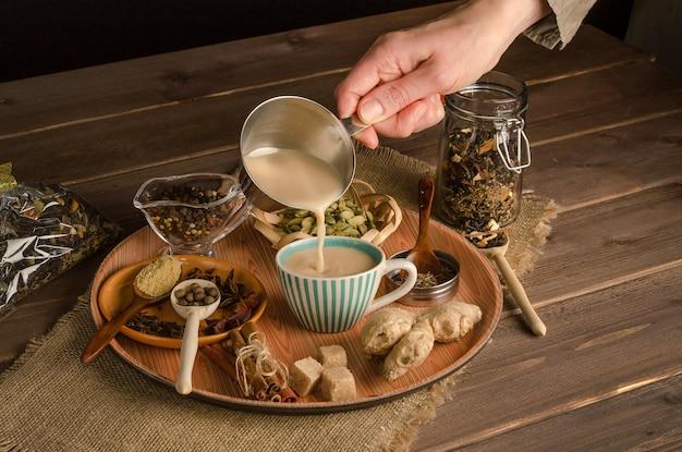 Femme verse du thé masala aux épices