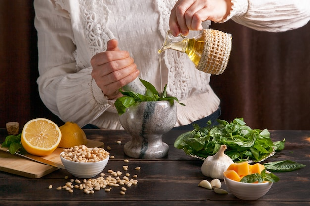Une femme verse de l'huile d'olive avec des feuilles de basilic dans un mortier pour faire une saucepesto
