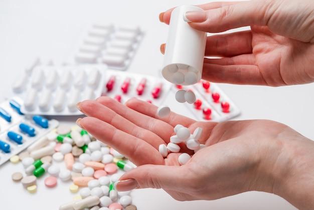 Femme verse des pilules dans sa main