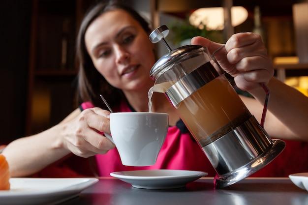 Femme verse le thé d'une théière dans une tasse