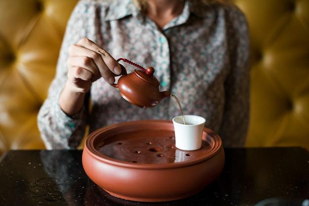 Femme verser du thé dans une tasse