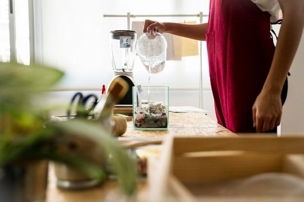 Femme verser de l'eau dans un récipient rempli de papiers déchirés