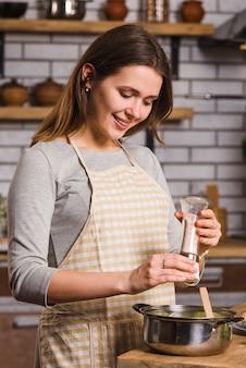 Femme, verser, épices, dans, pot, pendant, cuisine