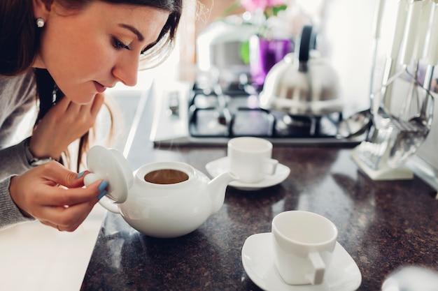 Femme, verser, thé, céramique, tasse, table