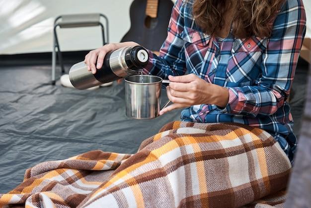 Femme verser le thé de thermos en tente de camping