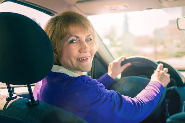 Une femme en veste bleue conduisant une voiture traversant la ville.
