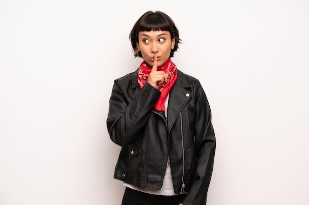 Femme avec une veste en cuir et un mouchoir montrant un geste du silence
