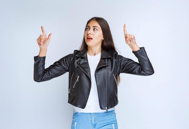 Femme en veste de cuir pointant vers quelque chose au-dessus.