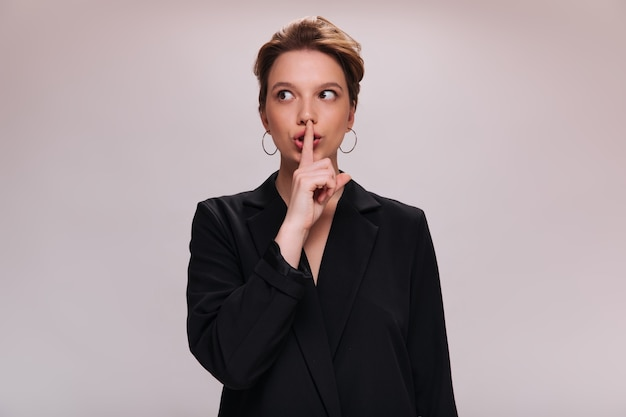 Une femme en veste demande à garder le secret. jolie fille en costume noir veut entendre le silence. dame en tenue surdimensionnée pose sur fond isolé