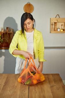 Femme en veste jaune déballant le sac eco mesh shopping