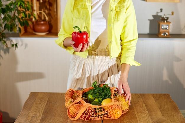 Femme en veste jaune déballant un sac écologique en filet avec des légumes et des fruits végétaliens sains dans la cuisine à la maison, concept végétarien d'alimentation saine.