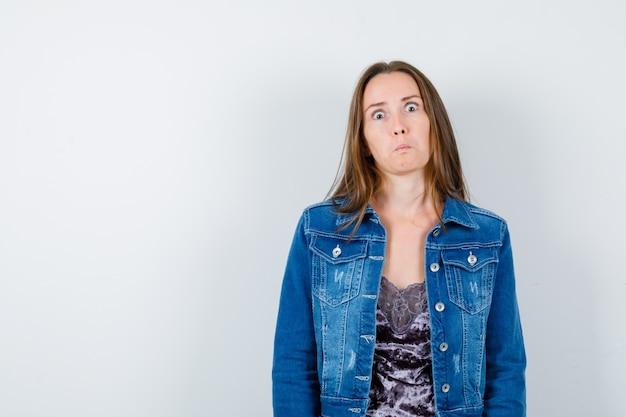 Femme en veste en jean, robe et choquée, vue de face.