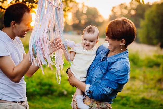 Femme en veste de jeans tient la petite fille tandis que le père joue avec elle