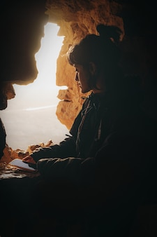 Femme en veste noire assise sur une formation rocheuse pendant la journée