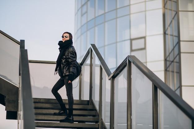 Femme en veste noire marchant à travers le pont