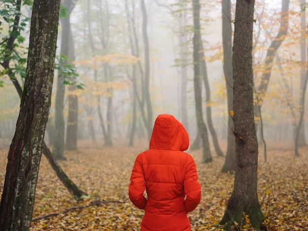 Femme en veste rouge à l'automne les feuilles jaunes marchent dans le brouillard