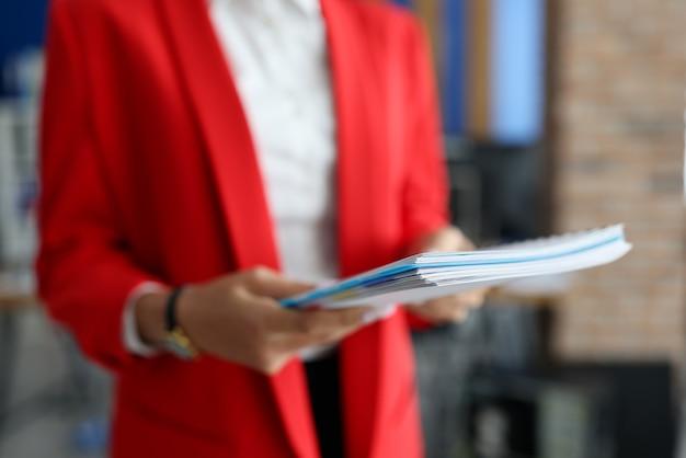 Femme en veste rouge détient des documents dans ses mains gros plan