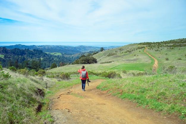 Femme en veste rouge avec sac à dos et caméra marche sur sentier dans un paysage magnifique