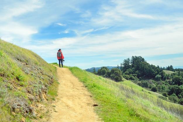 Femme en veste rouge avec sac à dos de randonnée sur sentier dans un beau paysage