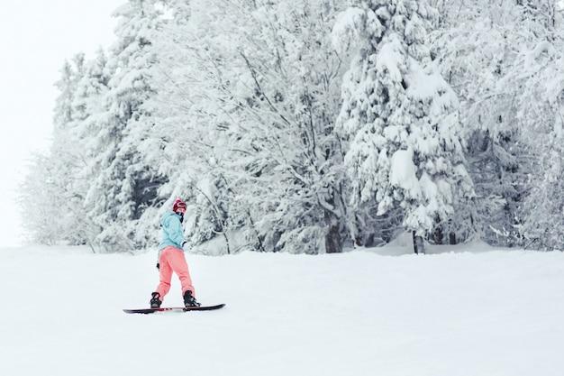 Femme en veste de ski bleu et pantalon rose se dresse sur le snowboard quelque part dans la forêt d'hiver