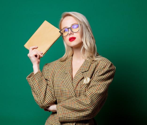 Femme en veste de style britannique avec livre sur mur vert