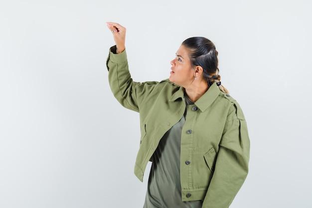 Femme en veste, t-shirt faisant semblant de tenir quelque chose de minuscule et à la recherche concentrée