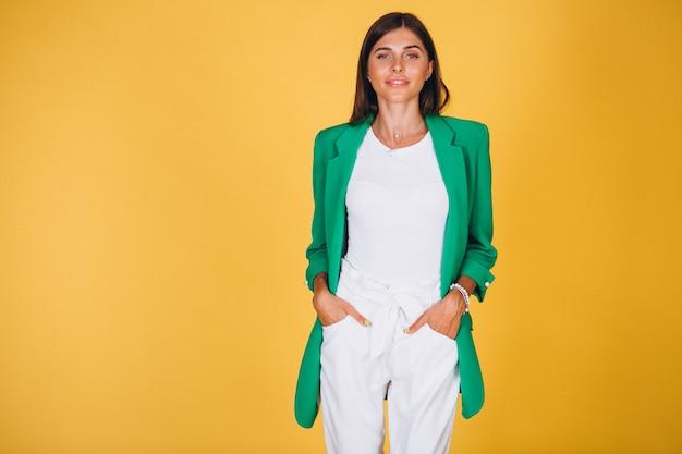 Femme en veste verte en studio sur fond jaune