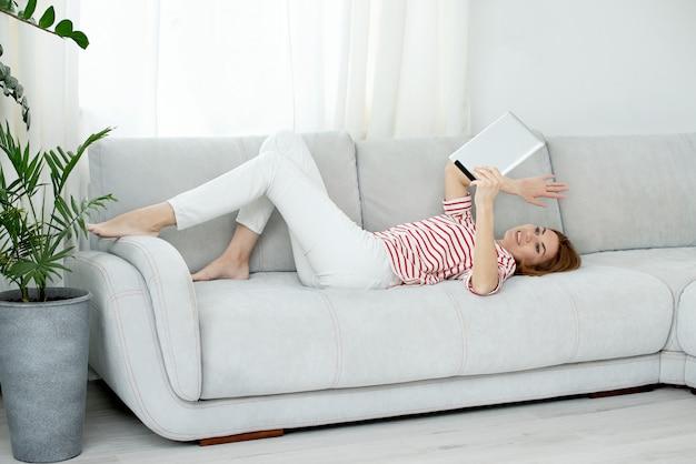 Une femme en vêtements blancs communique par liaison vidéo. discuter en ligne et saluer l'écran de l'ordinateur. quarantaine et auto-isolement dus au coronavirus.