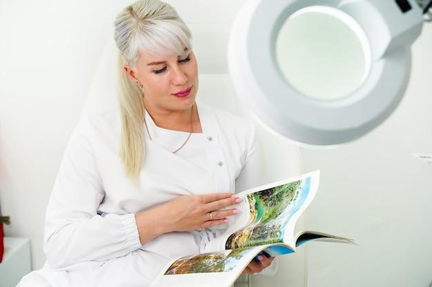 Une femme en vêtements blancs est assise sur une chaise dans un bureau à l'intérieur blanc et feuillette un magazine...