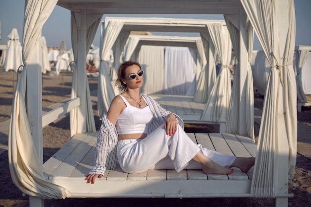 Femme en vêtements blancs et lunettes de soleil est assise sur la plage près des maisons en bois un transat intérieur avec un chiffon en vacances