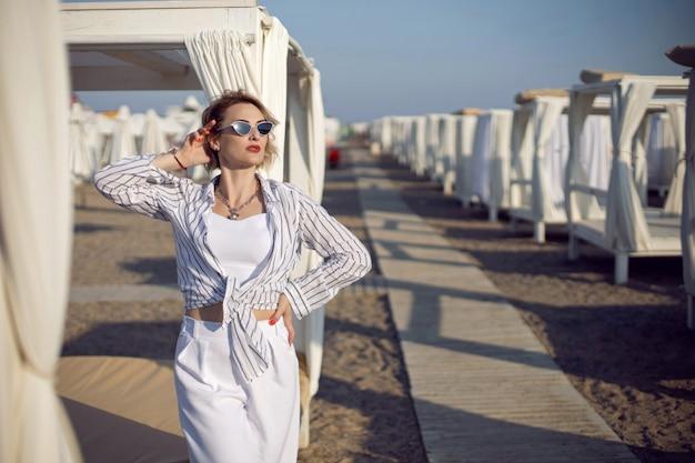 Femme en vêtements blancs et lunettes de soleil se tient sur la plage près de bois