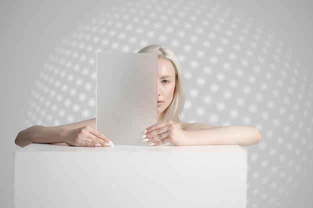 Une femme en vêtements blancs tient un gadget futuriste