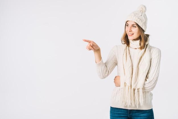 Femme en vêtements chauds pointant à côté