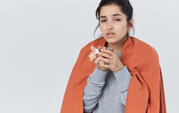 Femme en vêtements chauds avec une serviette à la main des problèmes de santé du nez qui coule une tasse de thé. photo de haute qualité