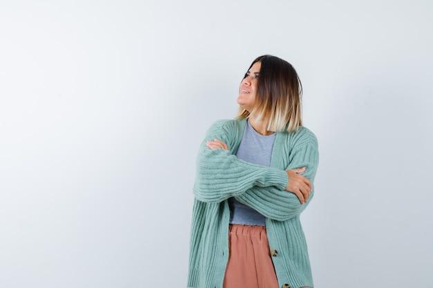 Femme en vêtements décontractés debout avec les bras croisés et à la rêveuse, vue de face.