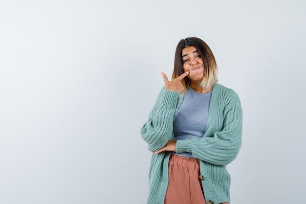 Femme en vêtements décontractés en gardant le doigt sur la joue soufflée et à la drôle, vue de face.