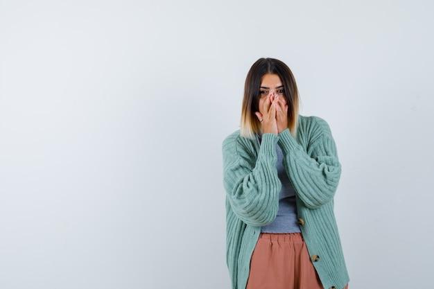 Femme en vêtements décontractés, gardant les mains sur la bouche et regardant excité, vue de face.