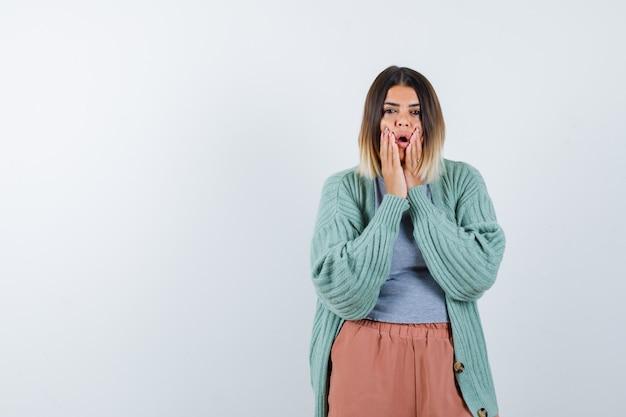 Femme en vêtements décontractés, gardant les mains près de la bouche ouverte et regardant perplexe, vue de face.