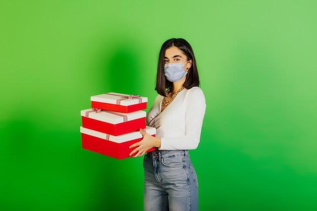 Femme en vêtements décontractés portant un masque médical debout près du mur vert et tenant des cadeaux.